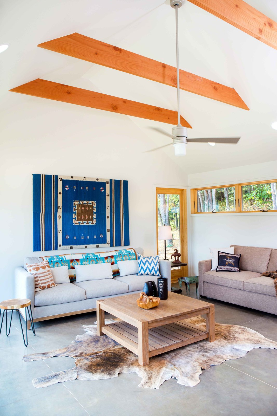 The bright ochres of the Douglas Fir beams and window framing accent the gray and white hues of the furniture, floors, and walls.  Habitats by Jenny Xie from Off-Grid Retreat