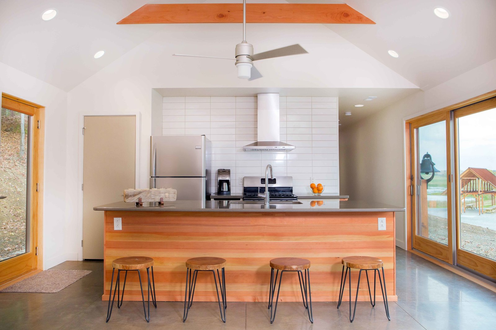 The kitchen island, also Douglas fir, showcases the material's rich striations and color variations. Behind the kitchen are two bedrooms and a single bathroom. A large open air pavilion, built concurrently with the cabin, can be seen from the windows on the right. Off-Grid Retreat by Zachary Edelson