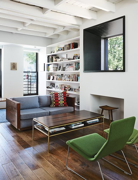 A vintage sofa purchased from Open Air Modern mixes with Low Pad chairs, by Jasper Morrison for Vitra, in the living room, which features a window inspired by Marcel Breuer's Whitney Museum of American Art.