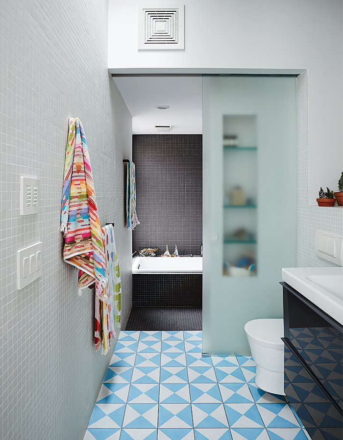 The second-floor bathroom includes a washroom that can be closed off from the bathing area with a sliding glass door. Bauer and Magid can supervise the kids' baths or use it as a steam room.  Photo 8 of 14 in Brooklyn Home Keeps its Historic Bones While Getting a Much Needed Interior Update