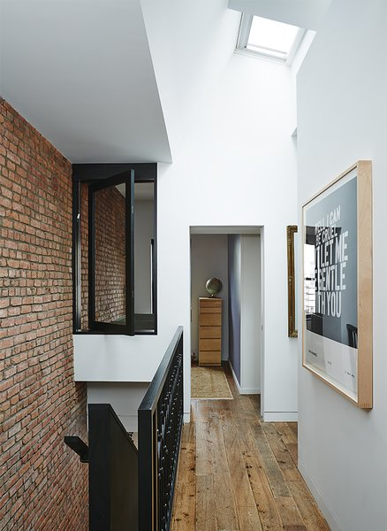An interior window creates flow between the skylit landing and baby Banks's room.