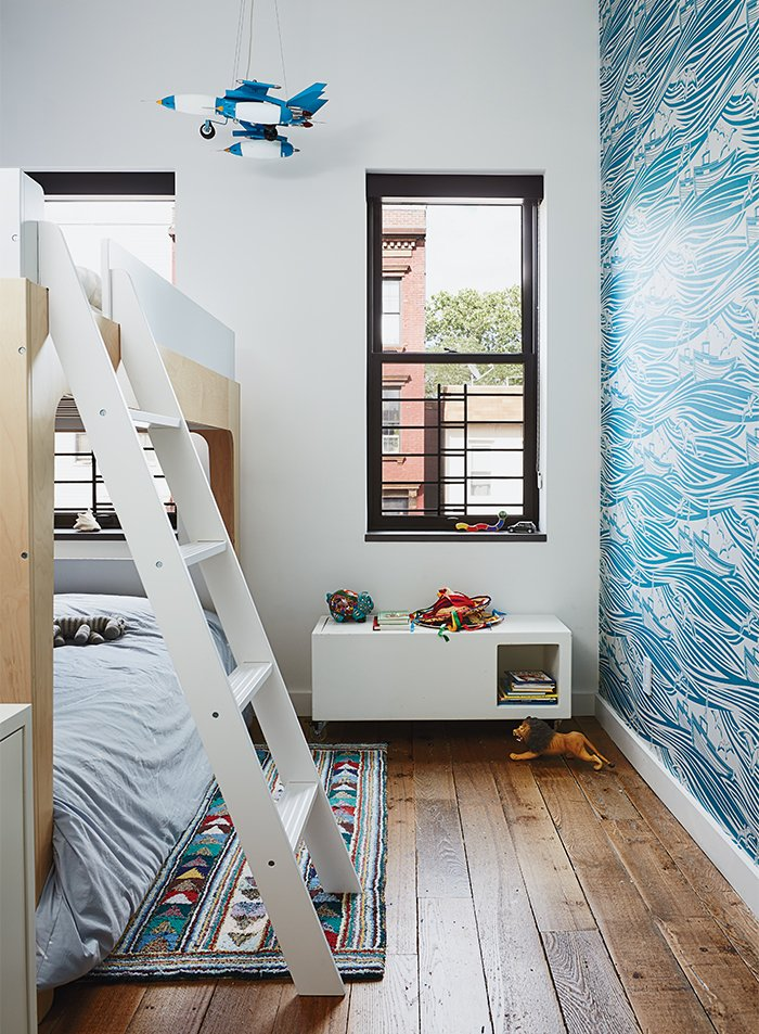 Magid selected lively Whitby wallpaper by Mini Moderns for Linus's room, along with Oeuf's Perch bunk bed. The homeowner found the light-up rocket-ship mobile on a trip to Mexico City.  Paint by Elizabeth Walsh from Wallpaper That Fixes Walls