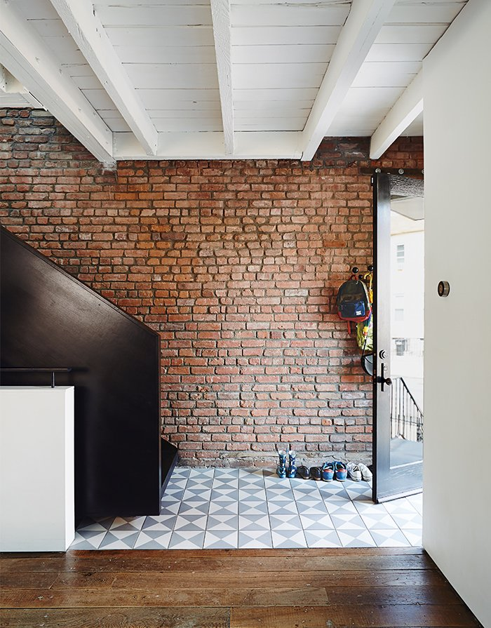 "Blackened steel for the Noroof-designed minimalist staircase matches the living room's ""Breuer"" window; reclaimed ash flooring came from a demolished church in Ohio. Tagged: Hallway and Dark Hardwood Floor.  Photo 13 of 14 in Brooklyn Home Keeps its Historic Bones While Getting a Much Needed Interior Update"