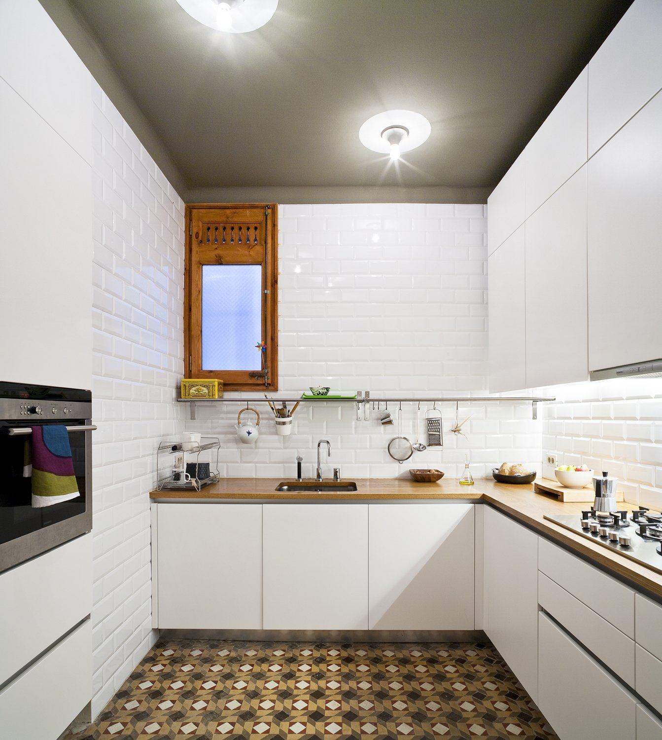"Since the original kitchen was not functional, the architects built a new one from scratch while preserving the original tiles. ""We designed very plain oak cupboards so the floor would be the protagonist,"" Eugeni says. Ceiling lamps by Vico Magistretti illuminate the warm wood countertops."