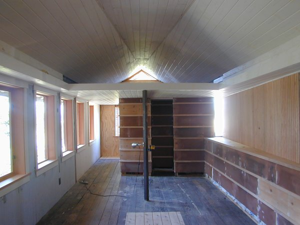 """Tiny 1920s Garage Transformed Into a Charming Studio - Photo 4 of 8 - BEFORE<br><br>After being used as an auto repair shop, the garage had been subdivided to include a dark storage area with an unsettingly low ceiling. Schaer opened up the space, replacing the collar ties in the rafters with a sloping triangular plane that Schaer says """"draws the eye from one end of the space to the other, increasing its perceived size."""" It's also utilitarian, providing natural ventilation by funneling hot air up through a triangular vent window."""
