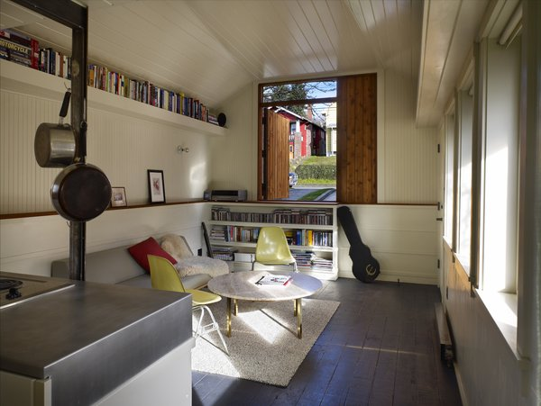 """Tiny 1920s Garage Transformed Into a Charming Studio - Photo 5 of 8 - The compact rental features plenty of wooden ledges, nooks, and shelves for keeping belongings organized. In the living room, a low white wall is capped with fir wood salvaged from the garage's former posts. On the east wall, a half-door made of reclaimed cedar looks out on a garden.  """"It looks and lives a lot bigger than it is,"""" Schaer says."""