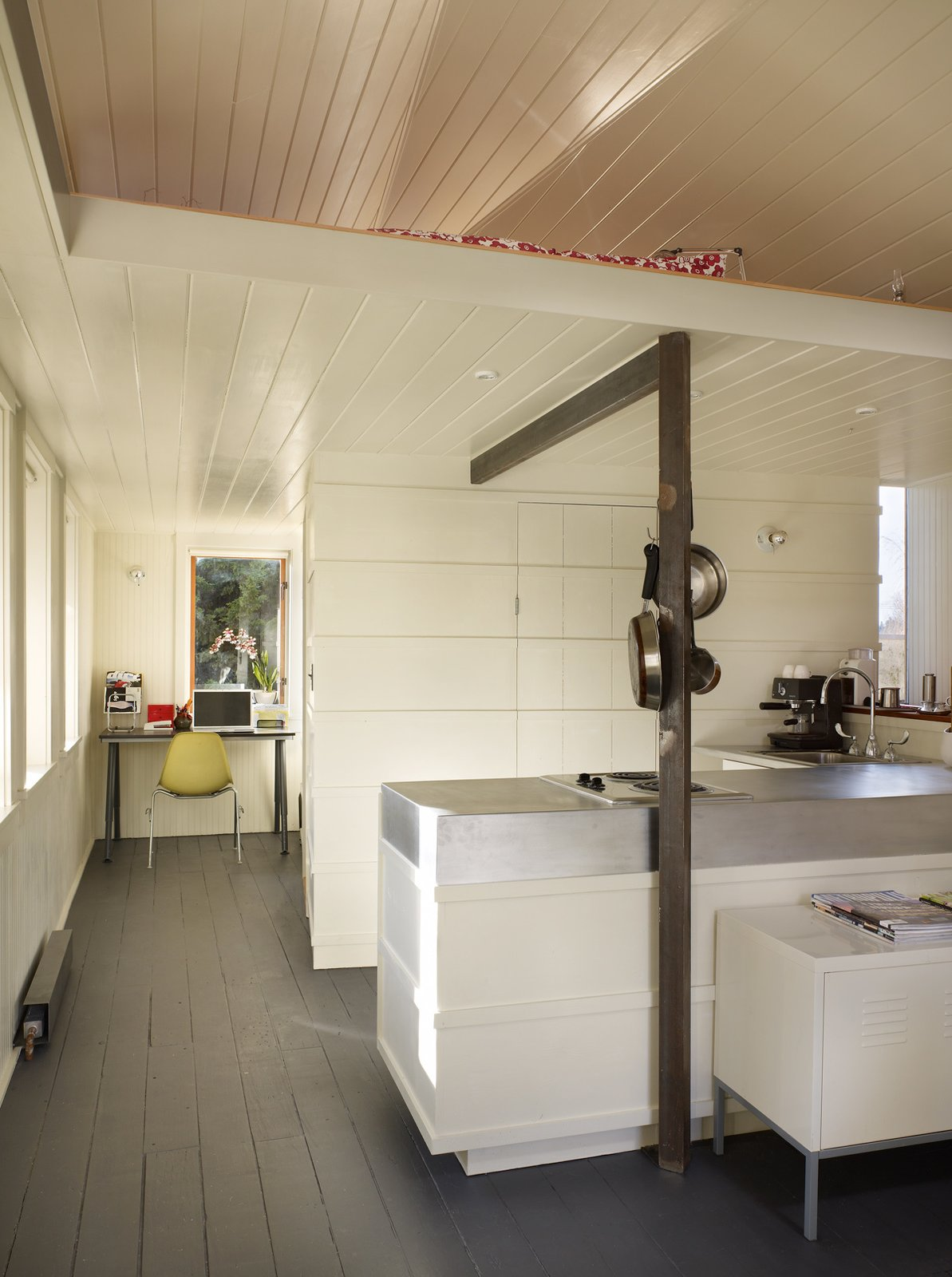 A utilitarian core contains the kitchen, bathroom, closet, and loft ladder. The kitchen's walls are clad with recycled wooden boards trimmed with horizontal battens that hide the oven and refrigerator from view.  Photo 6 of 8 in Tiny 1920s Garage Transformed Into a Charming Studio