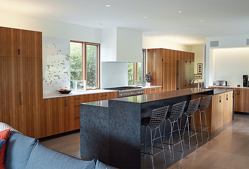 Bertoia barstools are tucked under a custom honed-granite kitchen island by a local company, Carthage Stoneworks. Hufft's team designed and built the larch cabinets. The appliances are by Thermador.  Photo 3 of 10 in This Kansas City Home Looks Like Its Neighbors, But Reveals a Truly Modern Sensibility