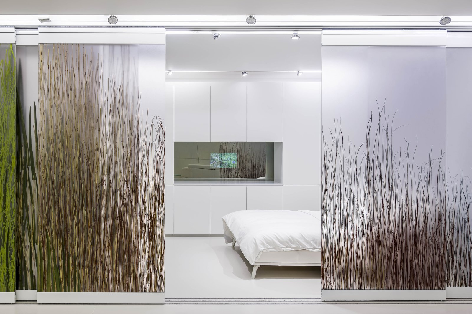 """A defining feature is the """"green wall,"""" a nearly 50-foot expanse of sliding panels that, when closed, presents a panoramic image of a natural landscape.  Bedrooms by Dwell from A Vision of the 'Apartment of the Future' From Poland"""