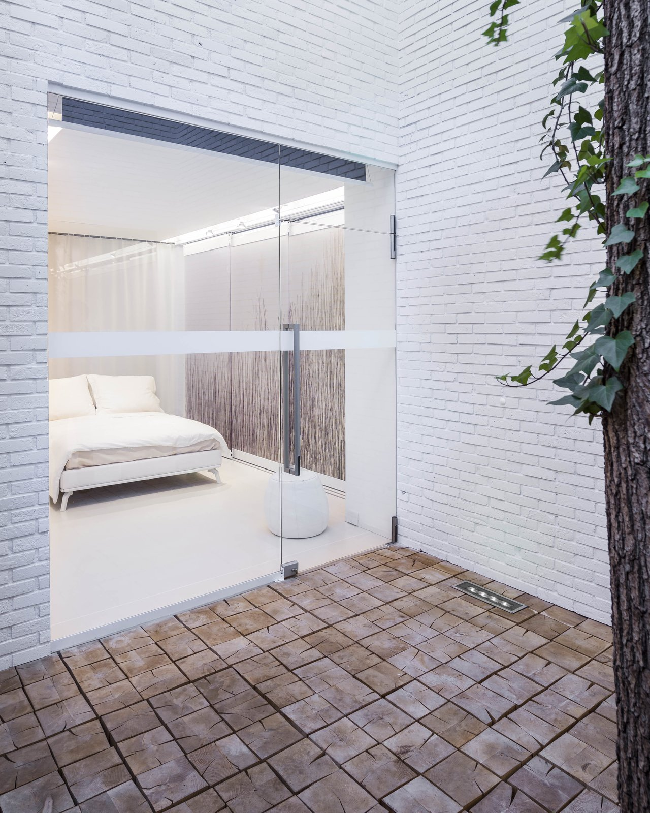 A view of one of the bedrooms from a courtyard. Bedrooms by Dwell