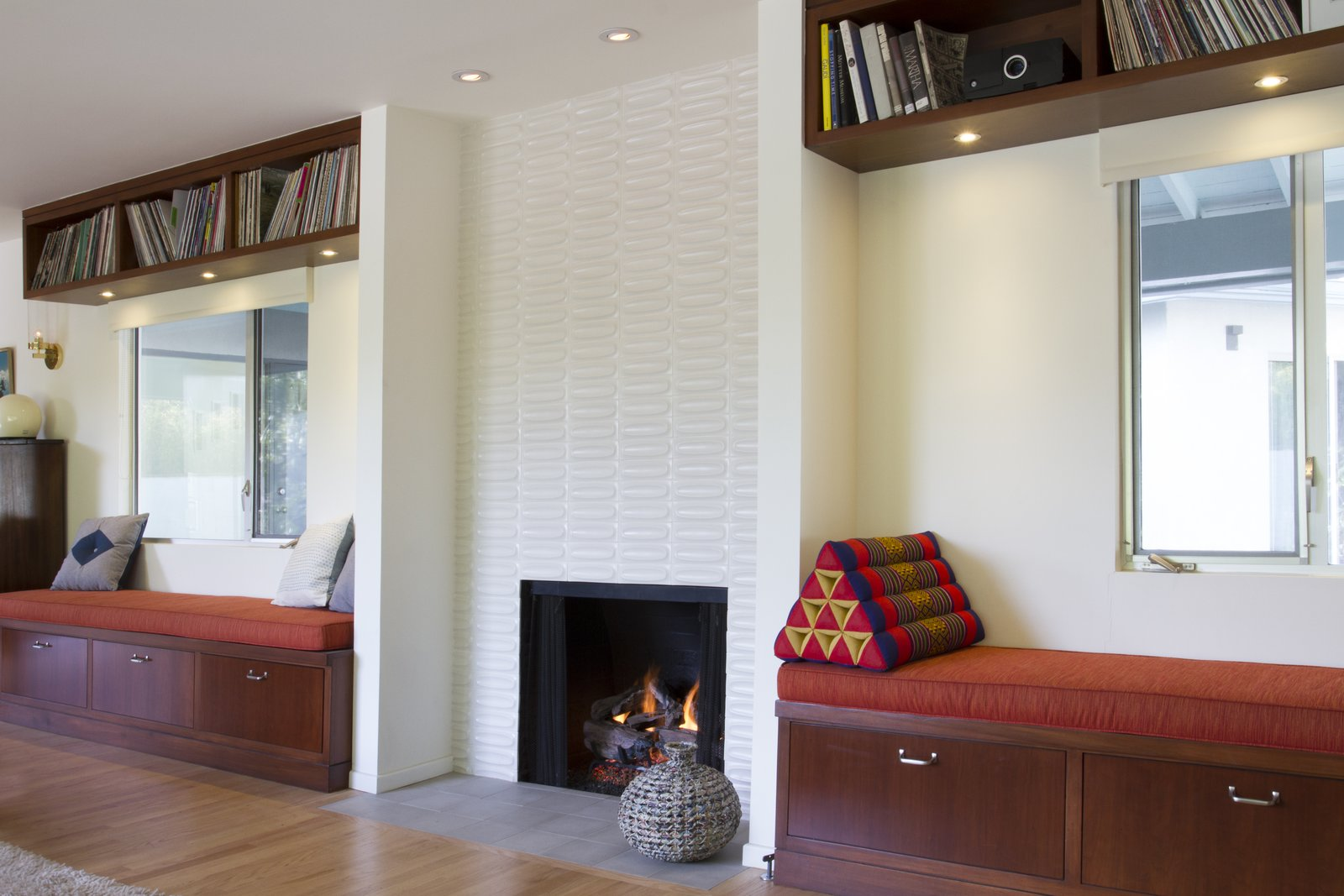 The panoply of tile continues in the living room, which is anchored by a second fireplace that Karen wrapped in oval Heath tile. The architects tactically preserved the home's most worthwhile features and modernized the rest, such as the vinyl windows they replaced with natural milled aluminum.