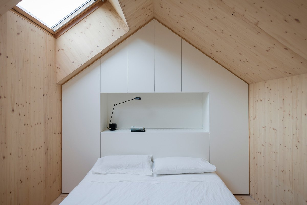 Each bedroom is designed to replicated a mini house, and follows the roof's pitch. A skylight lets in light. A custom unit made of white-painted MDF panels provides necessary storage. Tagged: Bedroom, Bed, Table Lighting, Light Hardwood Floor, and Shelves.  Vibey Architecture by Mark Mac from Bedroom Storage Ideas We Love