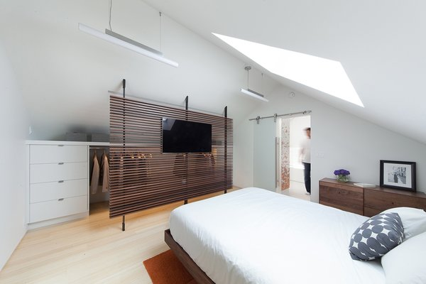 "In the master bedroom, a small, cramped closet was replaced with a wardrobe that is partially obscured by a slatted wooden screen that was built by Metalworks & Design Studio of Seattle. ""The idea was you see through it, so in a sense it doesn't feel like a small space,"" Smith says."