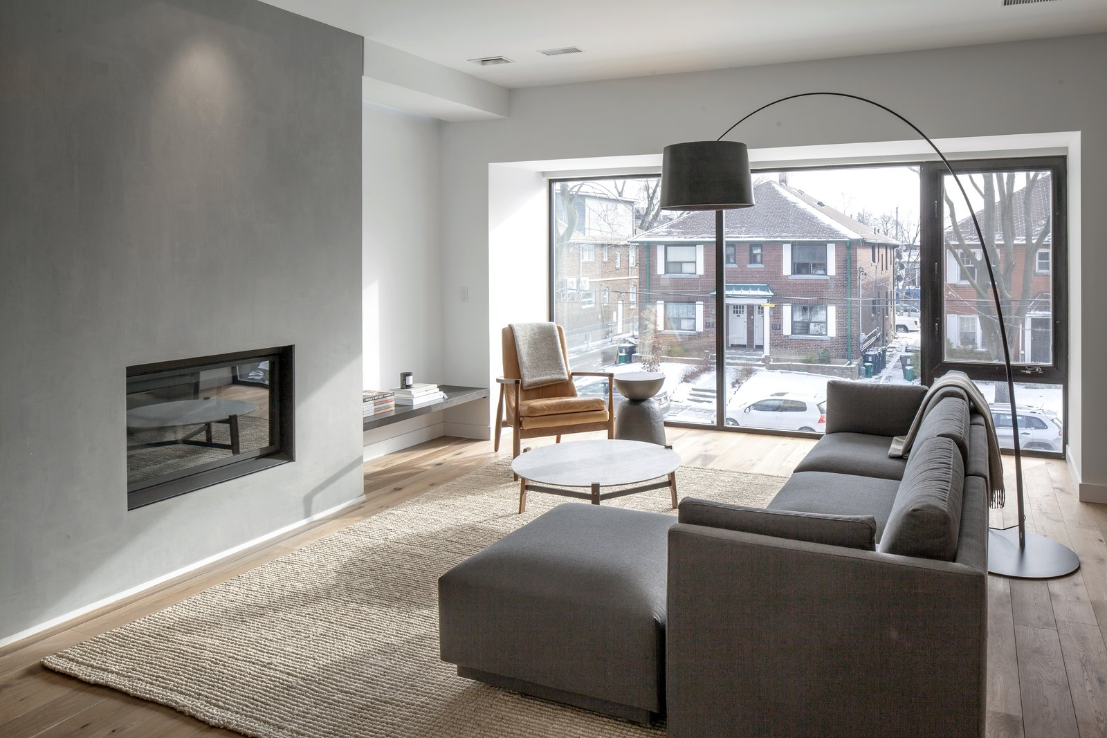 On the triplex's second floor, the homeowners' living room is framed by a sizeable bay window. The room centers on an EQ3 couch and Blu Dot's Free Range coffee table. A fireplace, finished with plaster, serves as a source of added warmth during the winter and a focal point all year round. The interiors were designed by Mason Studio. A Spacious Toronto Triplex Responds to Rising Urban Density - Photo 3 of 9