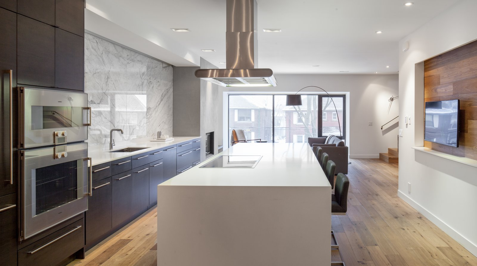 A spacious kitchen anchors the second floor. Its streamlined Cabico cabinetry and Gaggenau appliances direct the eye to the bay window and create an airy sensation. Quick meals can be eaten while perched atop the Cee stools at the Caeserstone countertop.  Photo 4 of 9 in A Spacious Toronto Triplex Responds to Rising Urban Density