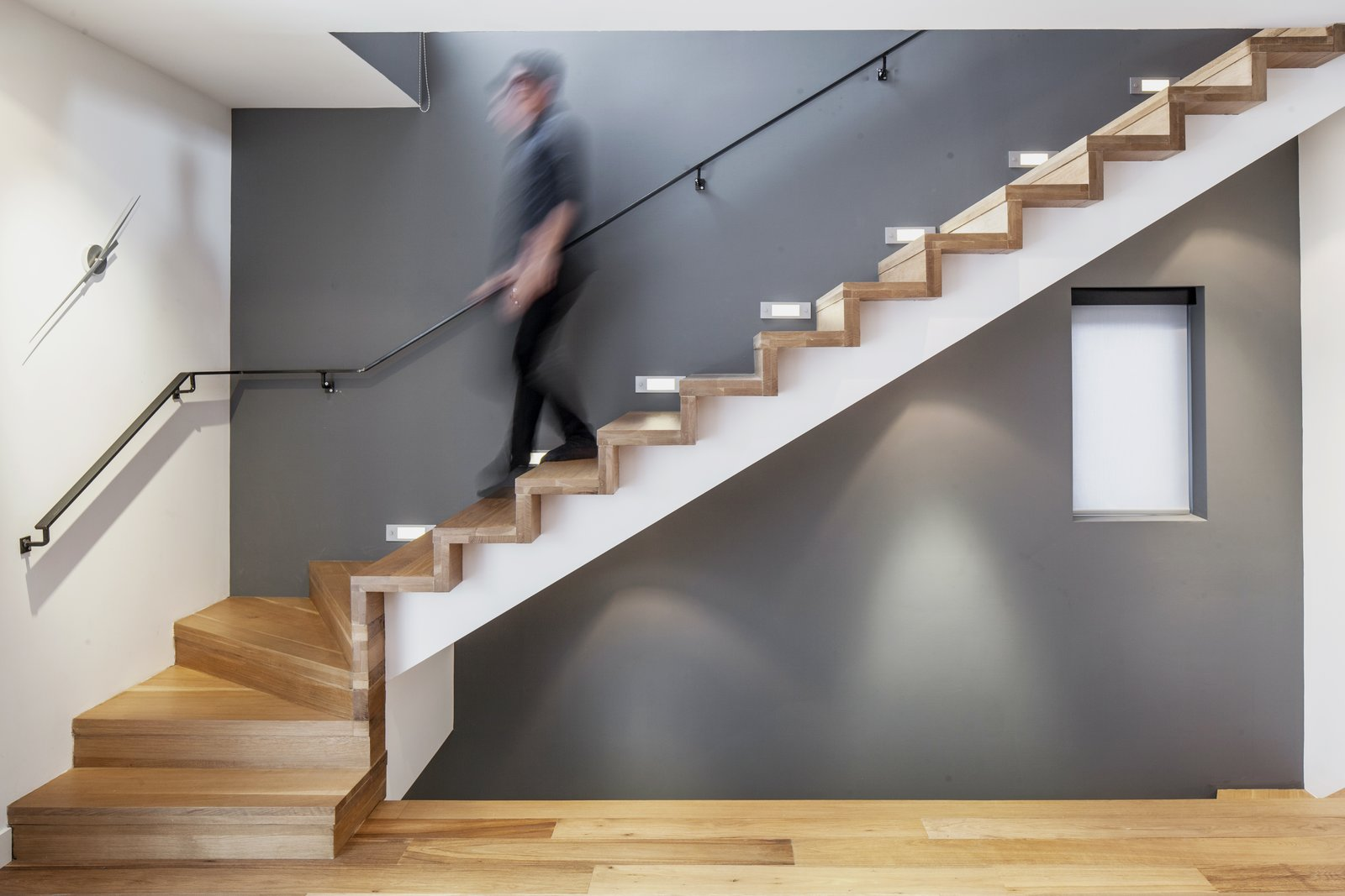 Behind the living room, a minimalist staircase leads to the upper level's bedroom and family room. White oak flooring unites the staircase and the rest of the living spaces.  A Look at Oak in 6 Modern Homes by Zachary Edelson from A Spacious Toronto Triplex Responds to Rising Urban Density