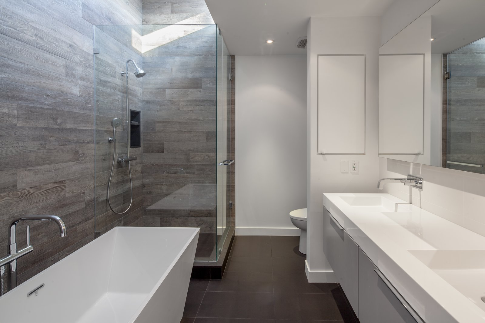 The soothing master bathroom is a vision in white and grey. On the walls, Statale 9 tiles by Viva blend the aesthetics of concrete and rough-hewn wood. This textural element contrasts with the crispness of the angular sinks and tub from Neptune's Wish Collection.
