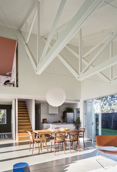 The inverted trusses subtly establish distinct spaces in the great room, with the bottom edges lending an intimate feel to the living area. A simple rice-paper lamp shade hangs above a kauri wood tabletop that the couple borrowed from Stock's aunt and uncle and set on a set of Taurus legs from Nils Holger Moormann. A Brit Longue chair by Sintesi isat right.