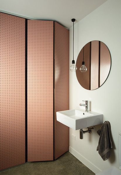 Sayes designed a pegboard screen to hide a bathtub and wash basin in the downstairs bathroom, and used the same shade of salmon-hued paint from Resene on the ceiling in the master bedroom. Sayes fashioned the pendant lamp from common parts, including a ceramic socket and a G125 incandescent lightbulb.