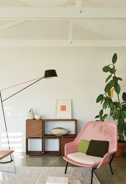 Sayes and Stock furnished their living area with a Slow Chair by Ronan and Erwan Bouroullec for Vitra, and a Spar floor light by Jamie McLellan for Resident. A print by Stephen Bambury sits atop a sideboard that Sayes built while studying at the University of Auckland.