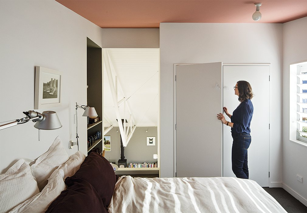 The master bedroom features an unobstructed door-sized opening onto the double-height great room. A pair of Tolomeo classic wall lamps from Artemide hang next to the bed. Tagged: Bedroom and Bed.  Photo 6 of 7 in A Dramatic Cutout Wall and Other Surprises Define This Playful House
