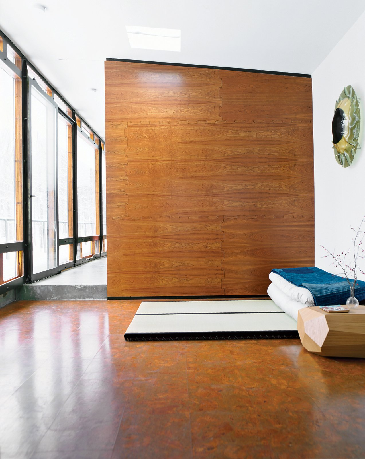 """For one of two sleeping areas flanking the main living space, Wooten placed tatami from Miya Shoji on the cork floor. """"With the radiant heating system, it's fantastic to be in this glass box looking out at a blizzard, walking barefoot on the warm floor,"""" he says. """"Tatami are not for everyone, but they are really comfy to me. Before we built the house, I stayed at a traditional bed-and-breakfast in Kyoto, Japan, and had one of the best nights of sleep ever, so I decided I wanted to do that style of bed. On top is a 150-year-old Japanese denim patchwork quilt I bought from a friend who took me to Japan. I've always admired Japanese design—Noguchi is one of my favorites—so I was inspired to have that spirit in the house."""" miyashoji.com  Photo 11 of 12 in A Hybrid Prefab Home in Upstate New York"""