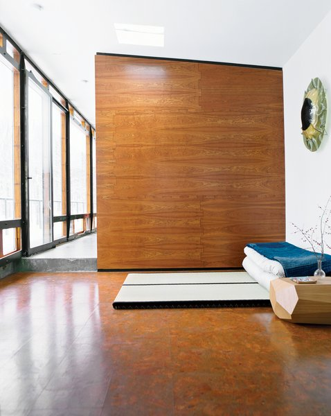 """For one of two sleeping areas flanking the main living space, Wooten placed tatami from Miya Shoji on the cork floor. """"With the radiant heating system, it's fantastic to be in this glass box looking out at a blizzard, walking barefoot on the warm floor,"""" he says. """"Tatami are not for everyone, but they are really comfy to me. Before we built the house, I stayed at a traditional bed-and-breakfast in Kyoto, Japan, and had one of the best nights of sleep ever, so I decided I wanted to do that style of bed. On top is a 150-year-old Japanese denim patchwork quilt I bought from a friend who took me to Japan. I've always admired Japanese design—Noguchi is one of my favorites—so I was inspired to have that spirit in the house."""" miyashoji.com"""