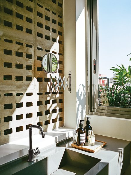 Perforated concrete blocks in the guest bathroom provide ventilation and discreet views of the patio.