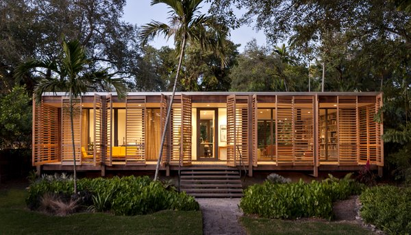 The 1,500-square-foot home features a striking interplay of sharp glass and soft wood shutters, creating a simple and practical building that's rich in cultural heritage. The home takes inspiration from many native building styles, including postwar tropical modernism, glass pavilion typology, and Florida cracker architecture. The dense ipe wood that clads the exterior and columns was chosen to withstand potential termite attacks and the damp tropical climate. Photo  of Brillhart House modern home