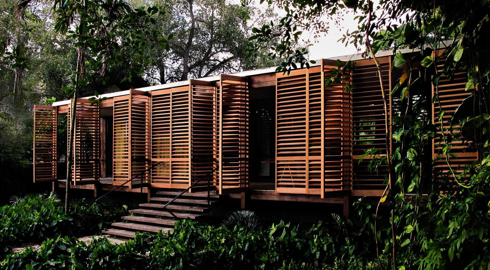 Lightweight shuttered doors made of western red cedar line the outer edge of the front porch, providing privacy and protection from the weather. The wood is left unstained, so it will age naturally in a way that's similar to the surrounding ipe wood. Just behind the shutter system, 50-feet of glass walls broken into four sets of sliding panels open to eliminate the barriers between indoor and outdoor spaces. Tagged: Exterior, House, Wood Siding Material, and Flat RoofLine.  Brillhart House by Emma Janzen