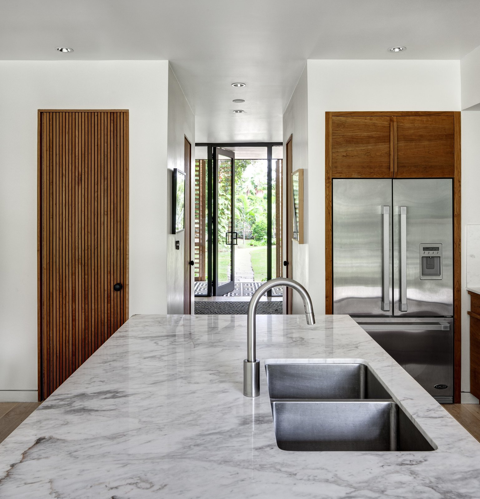 Himalayan marble countertops and stainless steel appliances lend moments of clean modernism to the kitchen, which is flooded with bright light thanks to patio windows that open to the yard. Tagged: Kitchen and Marble Counter.  Brillhart House by Emma Janzen