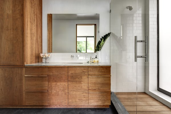 The master bathroom extends the same visual themes found throughout the rest of the home to keep the overall scheme unified. Ipe wood was used for the shower flooring and lightly oiled cherry wood forms the cabinets. Photo 6 of Brillhart House modern home