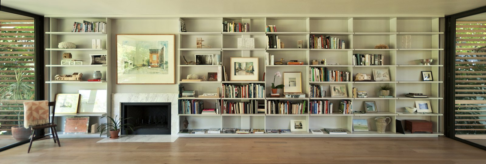 """In the living room, the Brillharts created a """"unified, simple and clean design"""" that incorporated a bookcase and fireplace along the continuous 30-foot long anchor wall. The shelves are inset several inches away from the glass walls on either side. Each individual layer cantilevers outwards to create a floating effect that mirrors the way the house itself floats above the ground."""