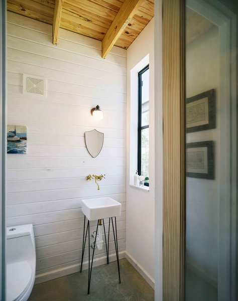 The sink in the half bath was special-ordered from Home Depot and Pavonetti designed the base to give the basin a snug fit. He built it out of a steel rod and painted it with black shoe polish.