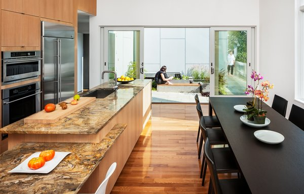 """To adhere to a limited budget, Höweler + Yoon used basic materials throughout—slate, concrete, wood, cement board—but splurged on a marble countertop in the kitchen. """"Because the house and millwork was so neutral to room could take a bit more richness,"""" says Yoon. From within the combined living/kitchen/dining area, one only sees the microcourtyard outside."""