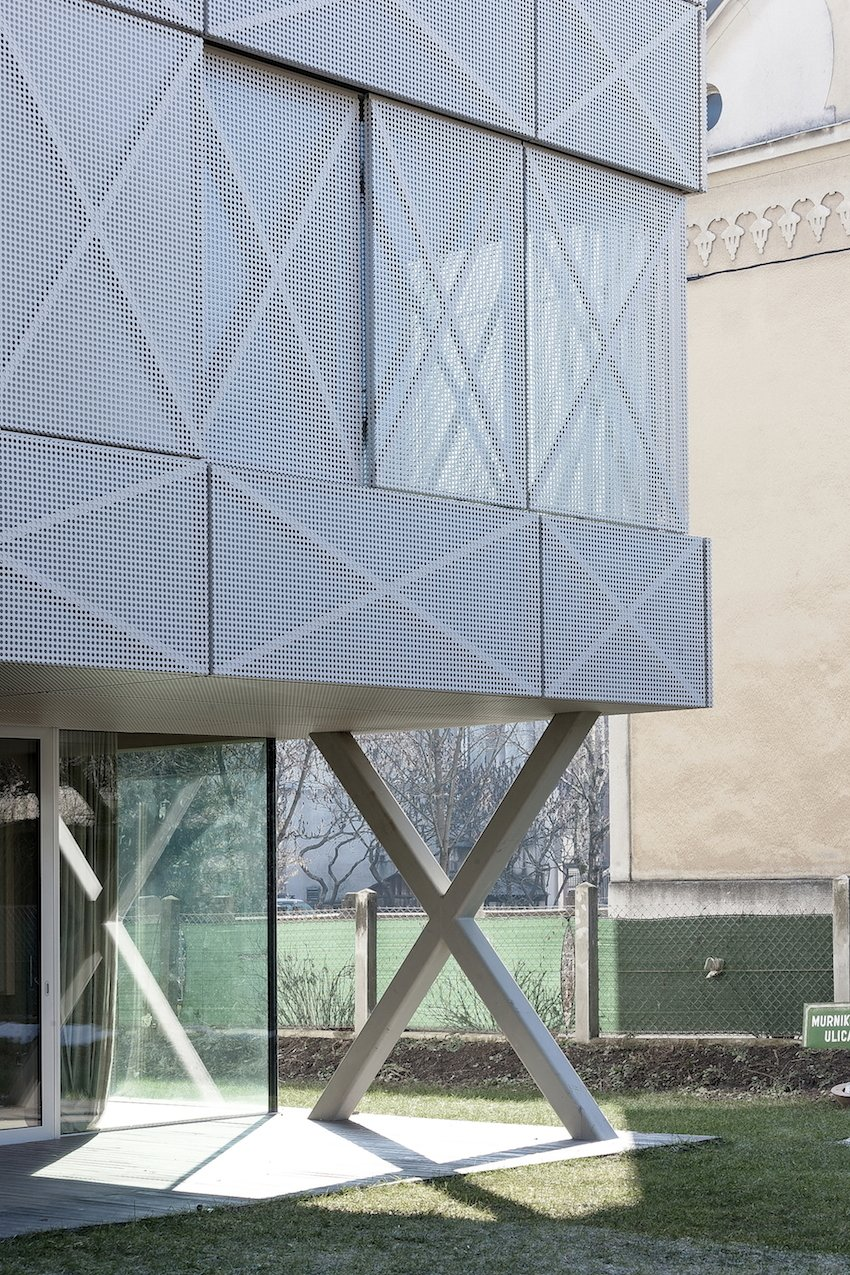 "Perforated steel panels provide a contrasting sense of roughness and lightness, which Oman played with throughout the home's design. The skin adds transparency and graphic energy to the exterior, though Oman did worry about people fixating on the tic-tac-toe element. ""It's like calling a rectangular building the Tetris house,"" he says."