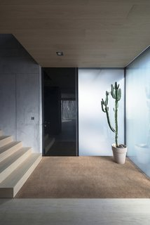 10 Fantastically Sleek Foyer Designs - Photo 2 of 10 - Wood, carpet, glass, and concrete: the entryway is a nexus of material and textures.