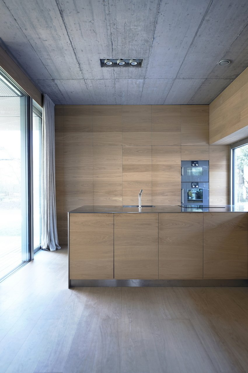 Oman and his partner Andrej Gregoric had the cupboards, stairs, and bed all custom-made. The interior casework provides storage and adds warmth to the concrete walls.  Photo 7 of 10 in Super Minimal Steel and Concrete Villa with an Unusual Facade