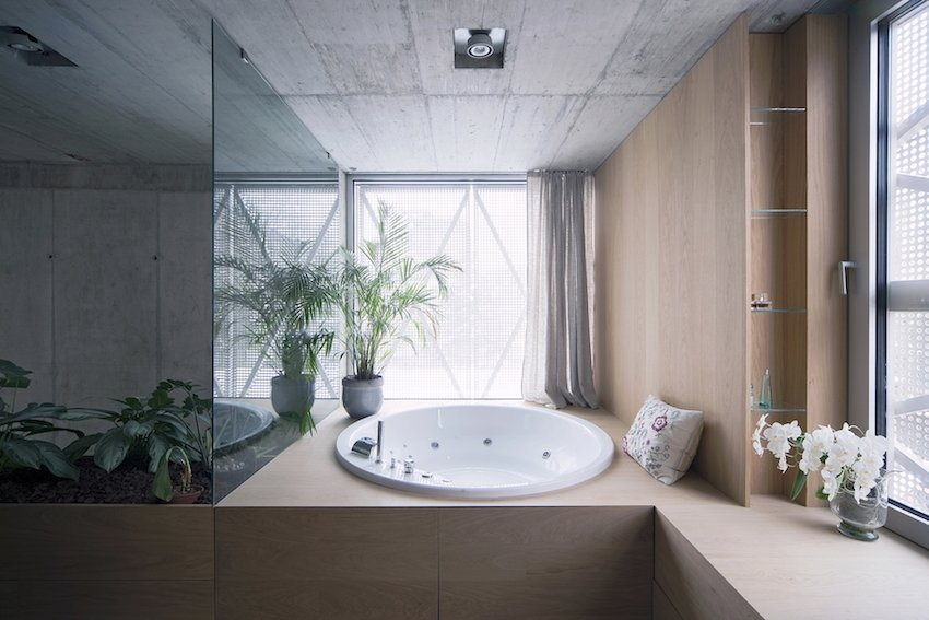 In the master bathroom, wrapped in custom oak casework, plenty of natural light permeates the steel panels. Tagged: Bath Room and Drop In Tub.  Photo 10 of 10 in Super Minimal Steel and Concrete Villa with an Unusual Facade