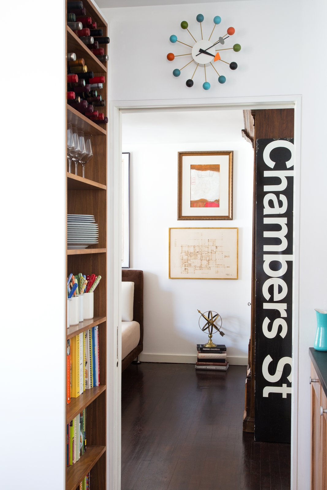 A Nelson Ball Clock and subway sign decorate one hallway. Tagged: Hallway and Dark Hardwood Floor.  Lovely NYC Abodes That Will Give You Apartment Envy by Allie Weiss from George Nelson's Ball Clock May Not Be His After All