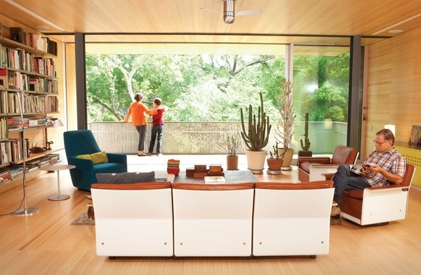 An architectural designer and an artist harnessed the collective power of their design firm to renovate a dilapidated mid-century gem into a hillside perch for their family.<br><br>Dieter Rams's modular 620 Chair Programme, from the 1960s, takes center stage in the Alford-Young family's living room. The set is accompanied by Artemide's classic Tolomeo floor lamp and a Portofino Bergère chair that was designed by Rodolfo Dordoni for Minotti. The rolling glass doors running the length of the room are from Fleetwood.<br><br>Photo by: Brent Humphreys