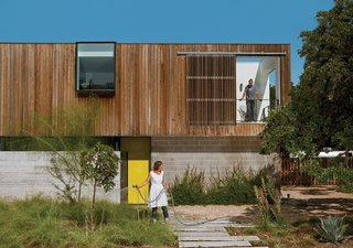 Austin couple Anne Suttles and Sam Shah built a house to last their lifetime—and longer. Mixing new efficient systems with old upcycled materials in their home, they keep it weird while keeping it green.<br><br>Here, Anne waters the bamboo muhly, palo verde, strawberry tree, and magic carpet thyme thriving in their yard.<br><br>Photo by: Brent Humphreys