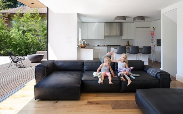 The addition of a living room beside the kitchen lets mom and dad spend more time with their kids – and watch over their activities. The children are sitting on a NeoWall couch by Living Divani, the light fixtures above the island are Smithfield by Flos, and the floor is oak. Photo 17 of Trotman Residence modern home