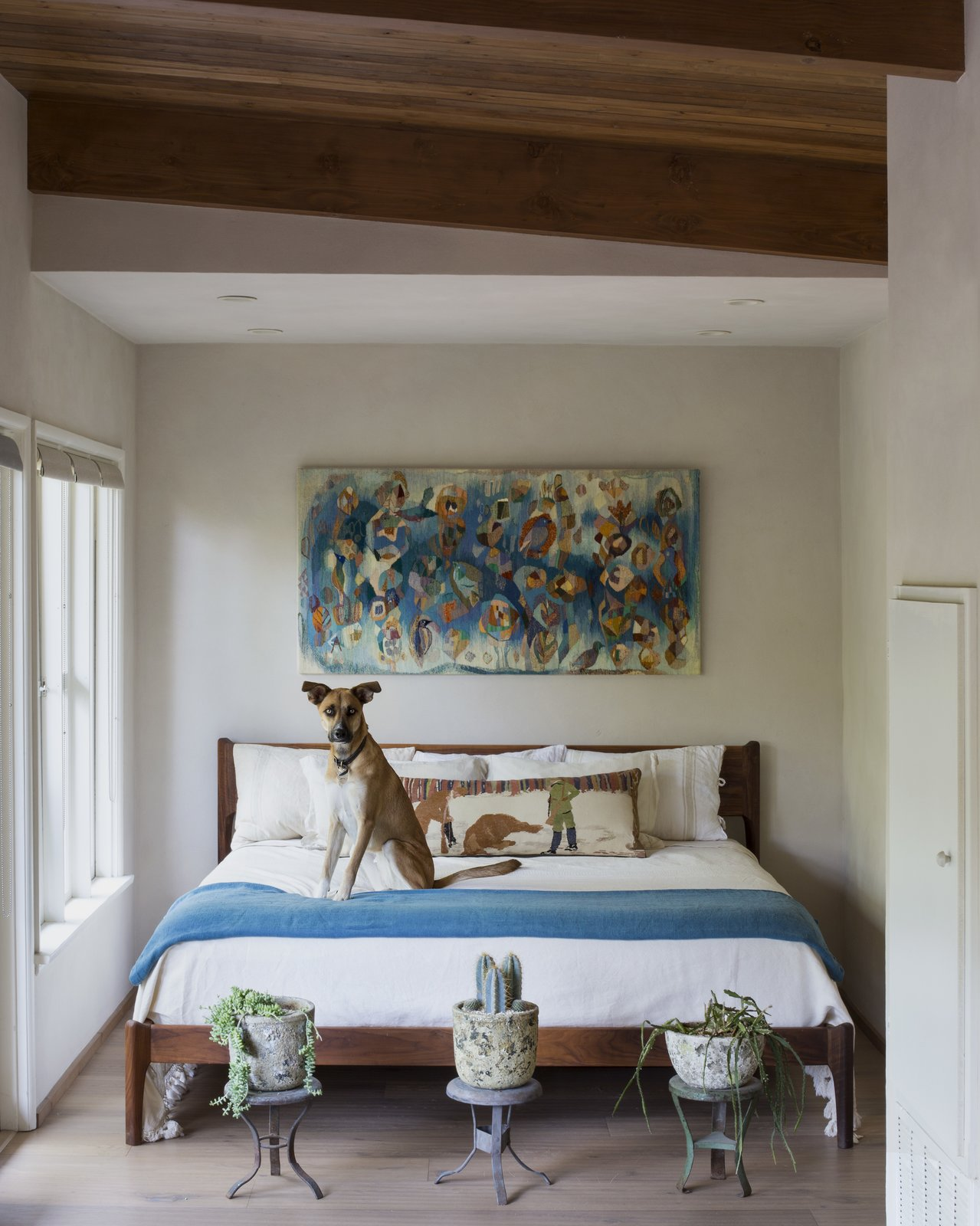 "Donut sits on a custom bed made by craftsman Pete Deeble. ""Above the bed I hung a vintage Evelyn Ackerman textile discovered on eBay,"" says Frank.  Bedrooms by Dwell from A Tiny House Remodel in a Bohemian L.A. Canyon"