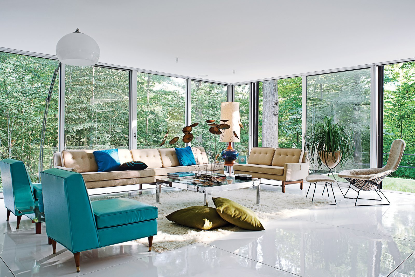 The spacious living room, filled with vintage furnishings by Harry Bertoia, Paul McCobb, overlooks the heavily wooded site, which adjoins a protected watershed. Photo by: Jason Schmidt