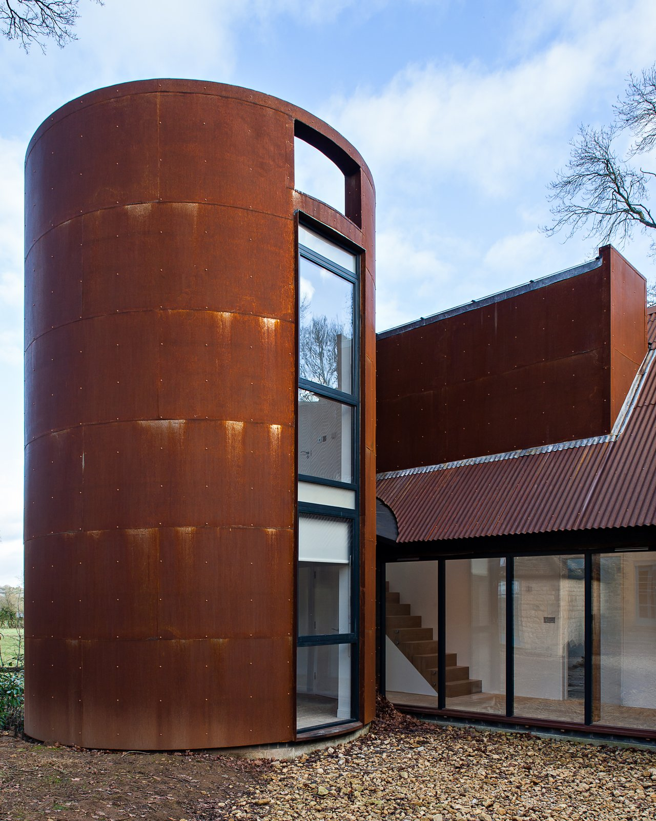 A circular tower echoes the former gas storage cylinder that once occupied its place. It houses a private study.  12 Ways to Get Creative With Cor-Ten Steel by Matthew Keeshin from This Modern Barn Looks Completely at Home in the English Countryside