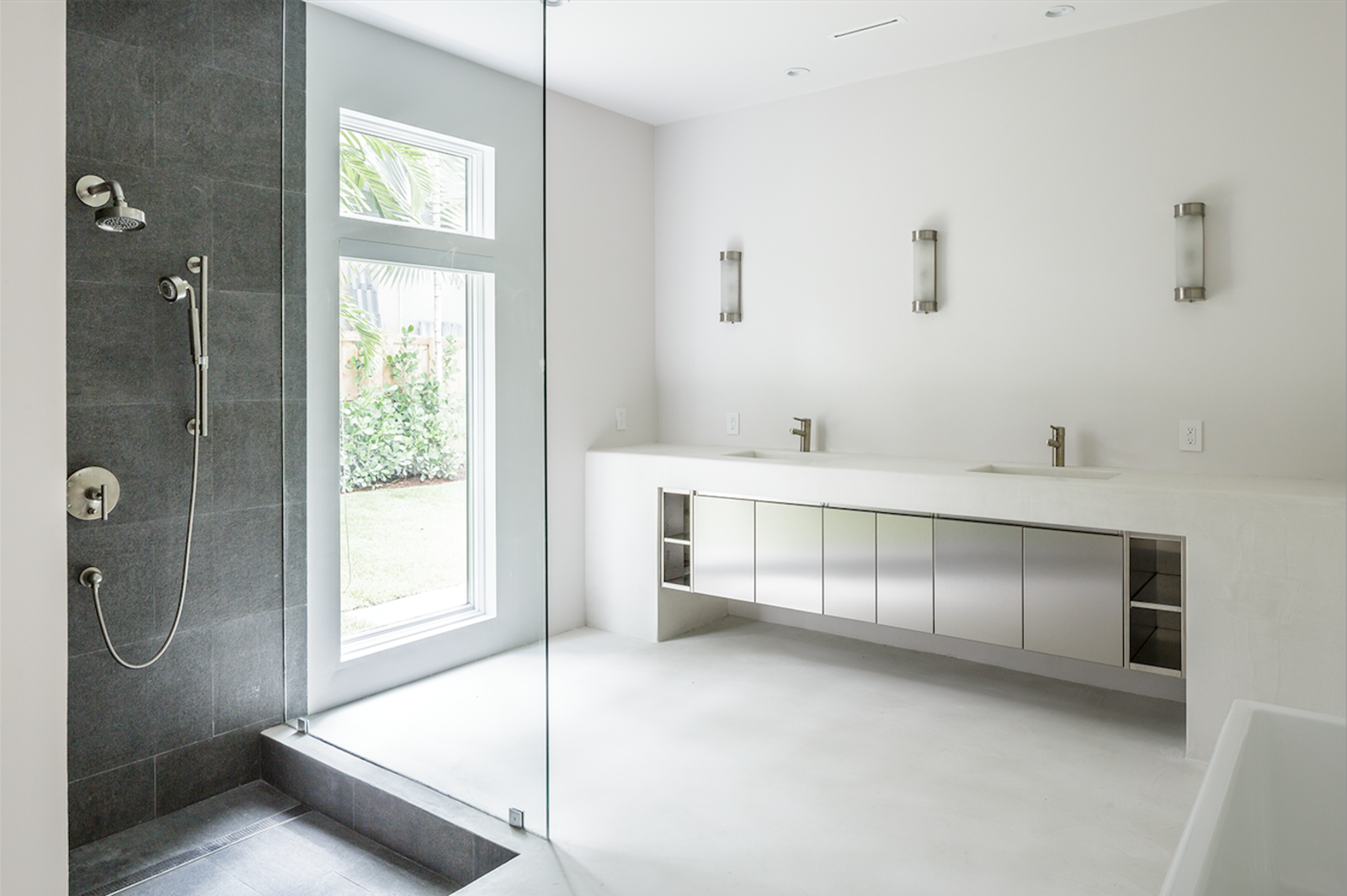 The bathrooms feature the same polished concrete flooring and poured concrete counters found elsewhere in the home. A honed granite recessed shower provides a visual counterpoint to the sea of white and steel. Bathroom by LSA