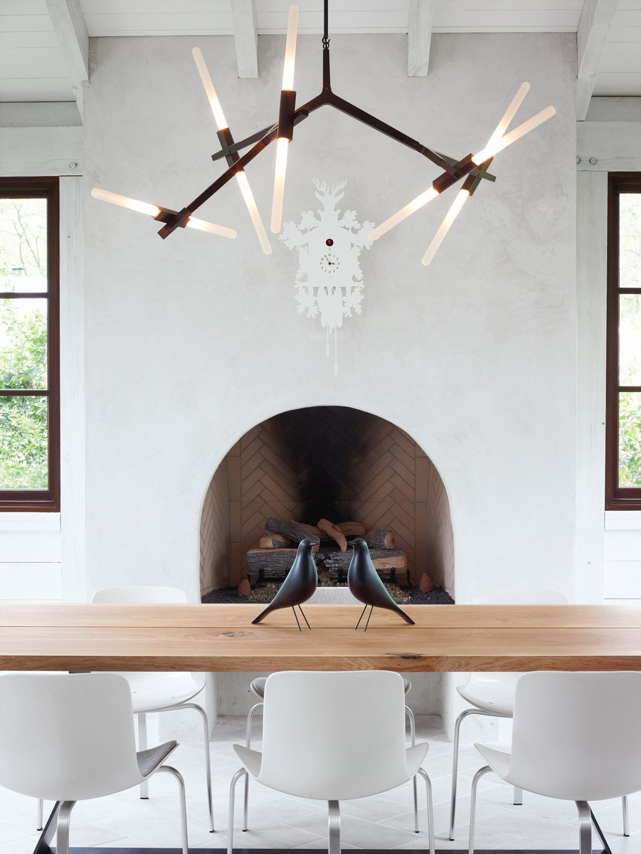 Barbara Hill designed this modern home in Atlanta, Georgia. Its informal dining space has a slightly rustic feel, sporting bronze and wood in the form of a Lindsey Adams Adelman chandelier for Roll & Hill.  127+ Inspiring Interior Ideas by Dwell from Lighting the Way