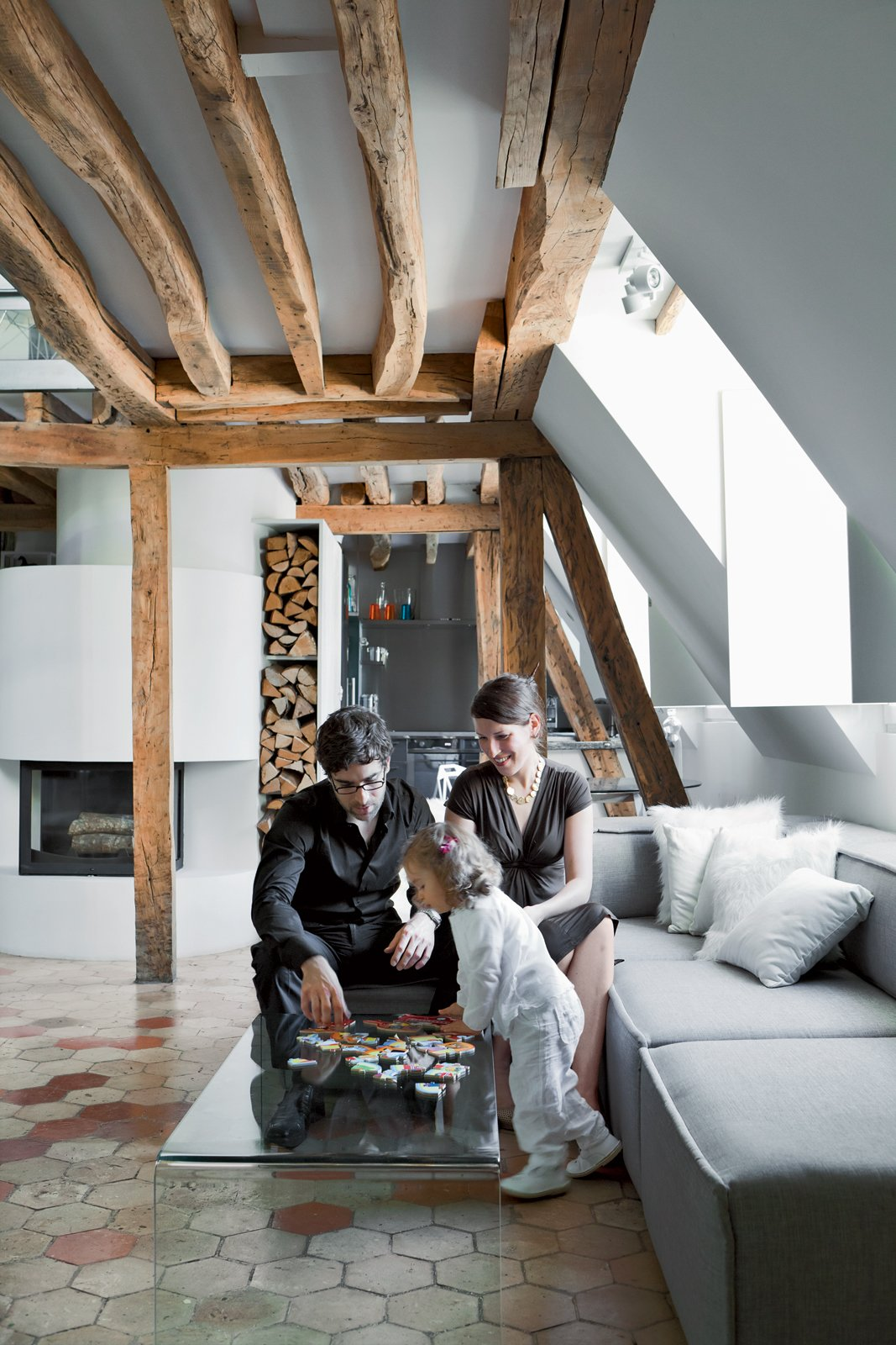 Herrman, his wife, Cécile, and their young daughter, Rose, play on the Pont table by Ligne Roset . The Carmo sofa is by Anders Nørgaard for BoConcept. Tagged: Living Room, Ceramic Tile Floor, Wood Burning Fireplace, and Sofa.  Photo 5 of 10 in 10 Modern Renovations to Unique Homes in France from A Corbusier-Inspired Parisian Home