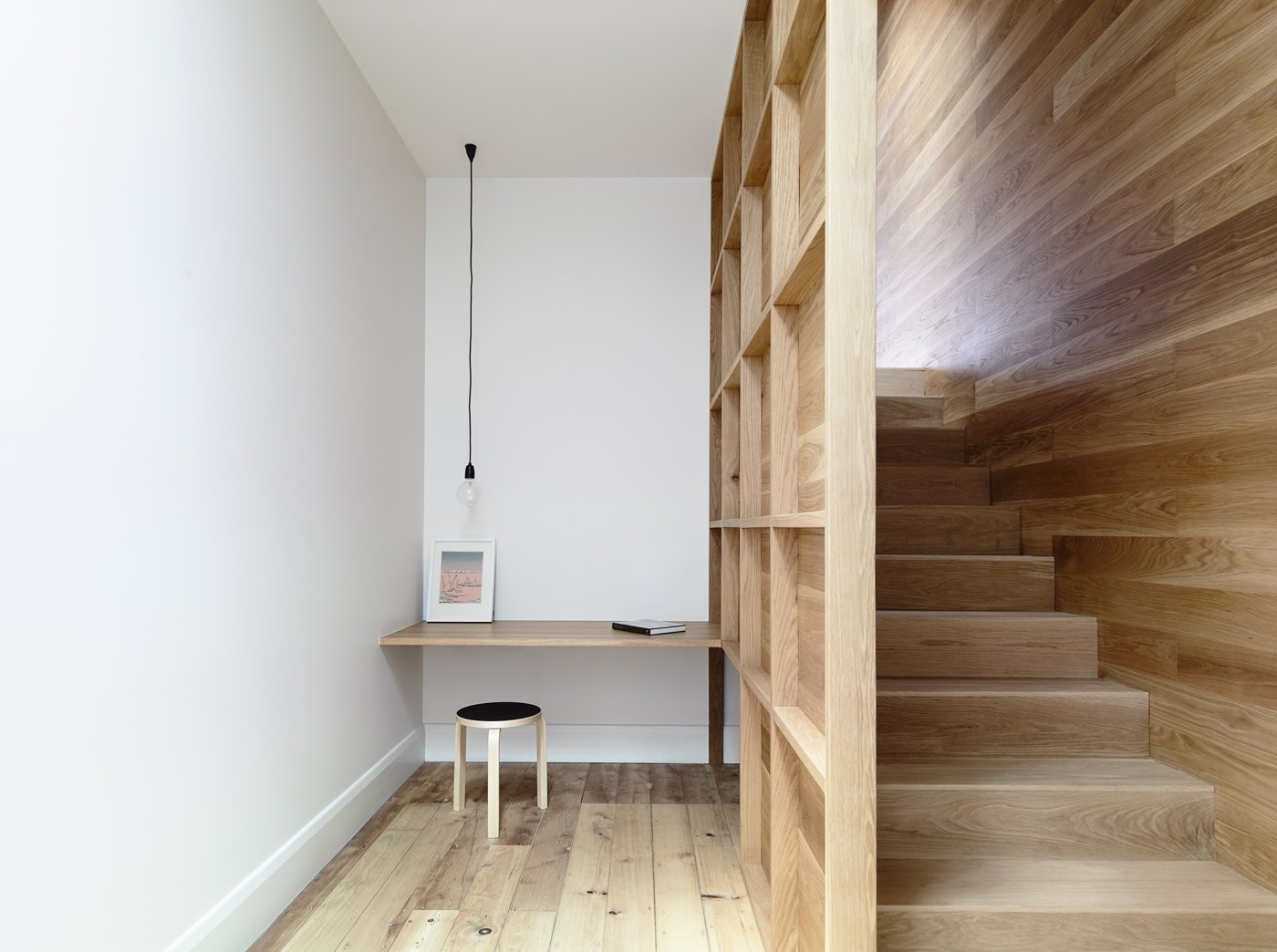 A central winding staircase connects the original house to the new addition. Exposed framing flanking the staircase creates an intimate study with plenty of shelving space. A Nud pendant light from Great Dane hangs above the built-in desk.